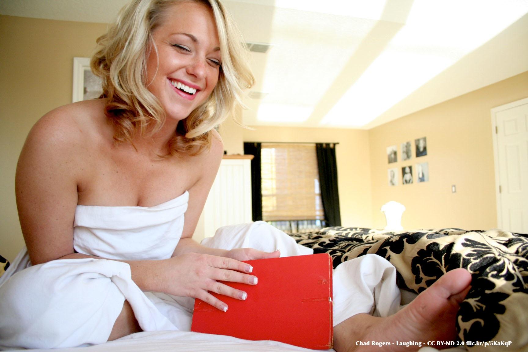 Foto di Chad Rogers con giovane donna bionda che ride, seduta sul letto con in mano un libro rosso